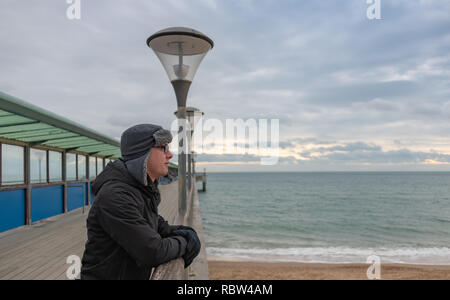 Bournemouth, Dorset, UK. 12th January 2019. Man in a warm hat looks out over Bournemouth from Boscombe Pier on a winters day. Credit: Thomas Faull/Alamy Live News - Stock Image