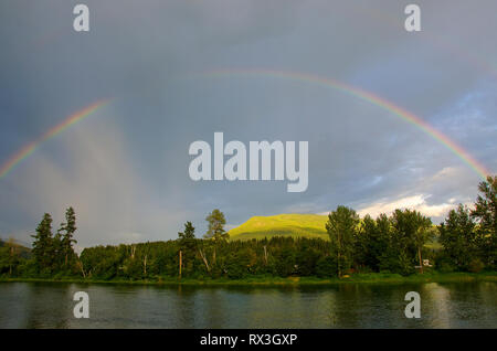 Rainbow appears over the Shuswap River in spring, near Enderby, British Columbia, Canada - Stock Image