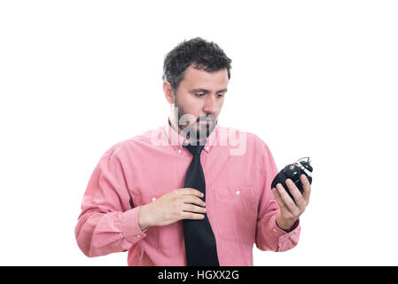 Angry young man holding alarm clock - Stock Image