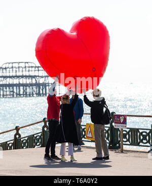 Brighton UK 30th April 2019 - An inflatable red heart is carried along Hove seafront to promote the 'Run for Love ' event which takes place on 1st June as they enjoy the warm sunny weather this morning with it forecast to reach into the high teens in some parts of the South East today. Credit: Simon Dack/Alamy Live News - Stock Image