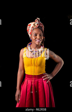 Portrait of a woman in African dress standing against a black background - Stock Image