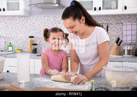 Happy Daughter Helping Her Mother Kneading Dough On Kitchen Counter - Stock Image