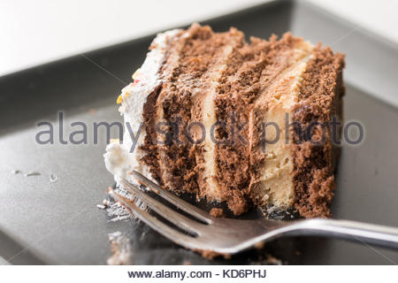 Slice of chocolate cake on the black plate with metal fork. - Stock Image