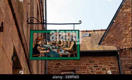 a pub bar card playing signpost in the historic picturesque medieval town of Moncontour, Brittany,  Northern France. - Stock Image