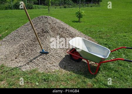 Construction wheelbarrow shovel on a pile of a rock gravel in a garden. - Stock Image
