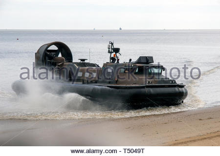 Military Hovercraft coming ashore on a sandy beach - Stock Image