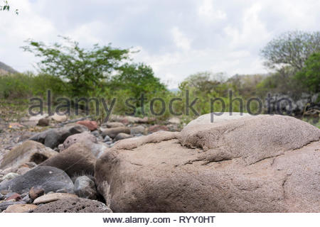 The dry season in Nicaragua, called 'verano' or summer, leaves river beds exposed between some residual pools, showing rocks like these. - Stock Image