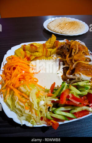 Shaverma, plate of lamb kebab with fries and salad, Saint Petersburg, Russia - Stock Image