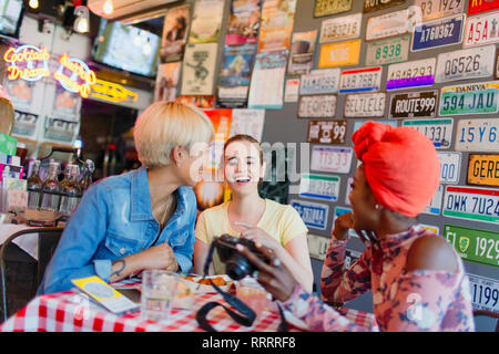Young women friends with digital camera in bar - Stock Image