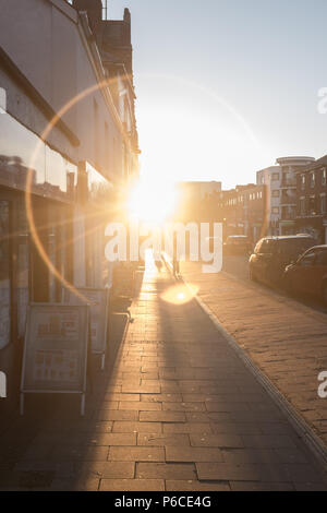 Ring of light shining on pavement through a road down a London street at Sunset as people go about their daily life, Hackney, England, Great Britain. - Stock Image