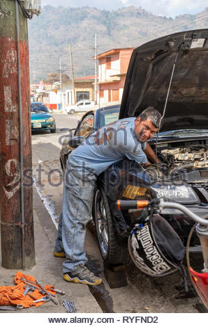 Mechanic works on a car in the street in Jinotega, Nicaragua - Stock Image