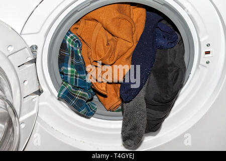 An automatic clothes washer with a lot of dirty clothes inside. - Stock Image