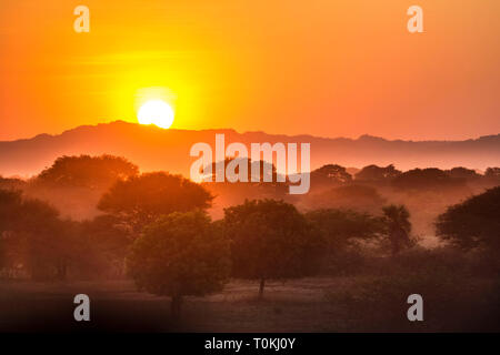 Sunset and dust over the Shan hills in Bagan, Myanmar - Stock Image
