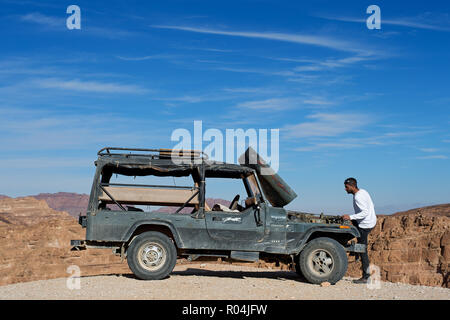 Man trying to repair his truck in Coloured Canyon. Nuweiba. Egypt - Stock Image