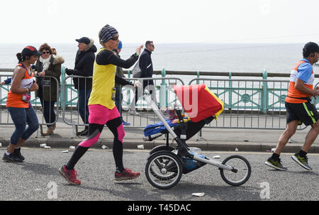 Brighton UK 14th April 2019 -   A woman with a baby in a pram takes part in this years Brighton Marathon which is celebrating its 10th anniversary Credit: Simon Dack/Alamy Live News - Stock Image