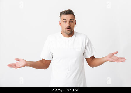 Image of puzzled man 30s with bristle wearing casual t-shirt throwing up hands isolated over white background - Stock Image