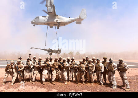Marines with Mike Battery, 3rd Battalion, 11th Marine Regiment, pose for a group photo in the dust of an MV-22 Osprey with Marine Medium Tiltrotor Squadron 268 (VMM-268) as it carries a M777 Howitzer during Marine Rotational Force – Darwin's Exercise Koolendong at Mount Bundey Training Area, Australia, Aug. 25, 2018. This is the first time an Osprey has lifted and moved a Howitzer in an austere environment in Australia and it is the first time an entire artillery battery deployed in support of MRF-D.    (U.S. Marine Corps photo by Staff Sgt. Daniel Wetzel) - Stock Image