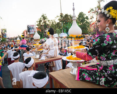 A woman in traditional costume being carried through the streets during the Chiang Mai Flower Festival parade in - Stock Image