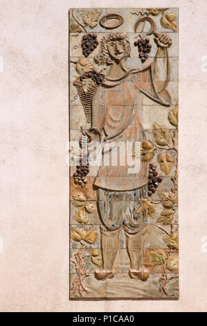 Relief design in tiles showing man in peasant dress ccollecgting grapes on facade of Domaine des Vins Place de la Halle, Beaune, France - Stock Image