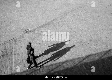 Blurred unrecognizable couple from above walking on an open space square with shadows projecting on the floor - Stock Image