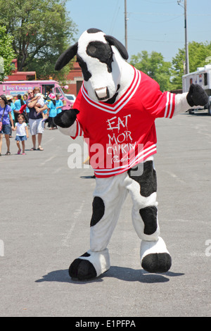 The Chick-fil-a cow is dancing at the International Festival and Fashion Show. - Stock Image