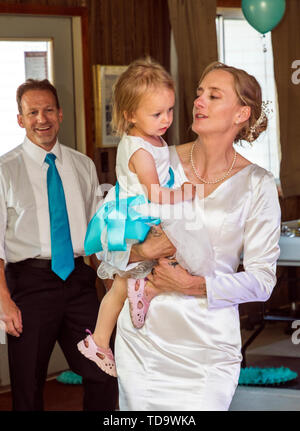 Bride holds young daughter; groom looks on; wedding reception;  Congressional Church; Buena Vista; Colorado; USA - Stock Image