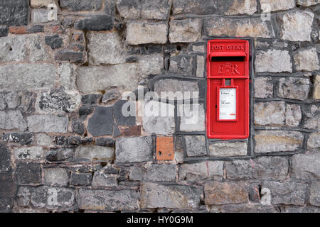 WINDSOR, UK - MARCH 18: A traditional iconic British post box in a stone wall in March 2017.. - Stock Image