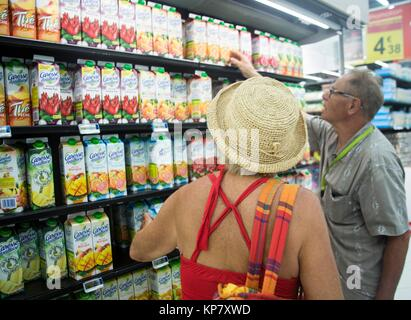 Caucasian woman and her husband buying grocery. and choosing their food carefully! - Stock Image