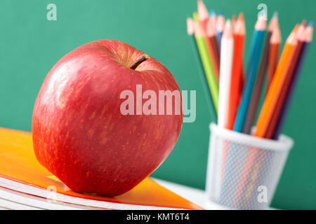 Close-up of big red apple on stack of copybooks with colorful pencils on background - Stock Image