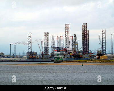 Jack Up drilling rigs at the TERRC Hartlepool  facility on the river Tees for repair and a construction vessel loading offshore windfarm parts - Stock Image
