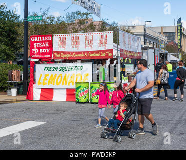 HICKORY, NC, USA-10/14/18: A father pushing a stroller with small boy, and with a pair of sisters holding hands, walks through an autumn town festival - Stock Image