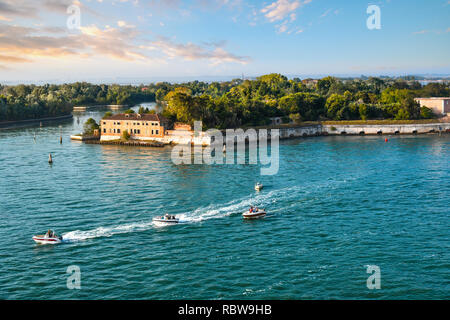 A group of small motor boats cruise past one of the outlying islands near Poveglia, in the waters off of Venice, Italy. - Stock Image