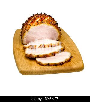 Sliced glazed ham on a board - Stock Image