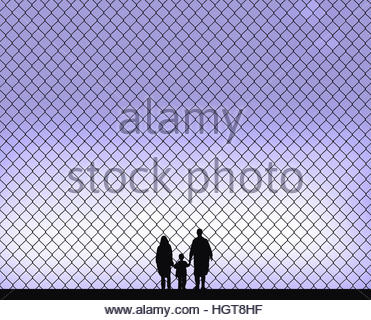 Family holding hands behind wire fence barrier - Stock Image