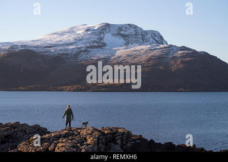 Walking the dog at Rhue looking towards Beinn Ghobhlach on Loch Broom, Wester Ross, Scotland - Stock Image