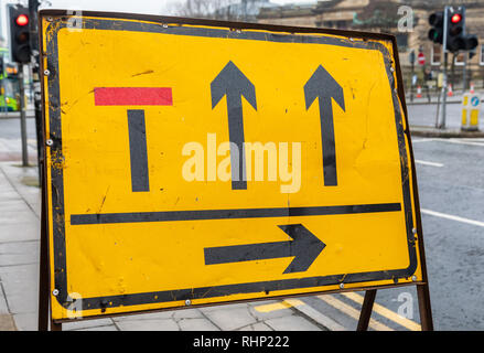 Yellow and black temporary street sign on pavement indicating lane closures due to roadworks Liverpool January 2019 - Stock Image
