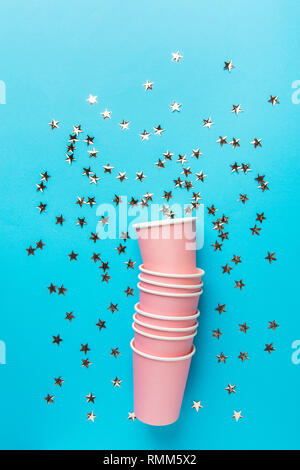 Stack of pink drinking paper cups on mint blue background glittering star shape confetti. Birthday party celebration holiday kids fun concept.Poster b - Stock Image