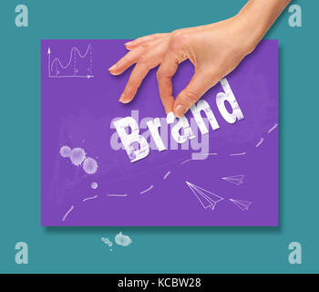 A hand picking up a Brand concept on a portable computer. - Stock Image