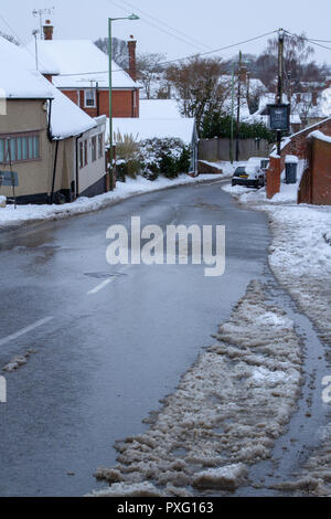 Suburban road on a snowy day - Stock Image