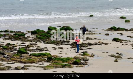 Two Photographers using tripods on the beach, Sennen Cove,Cornwall,England,UK - Stock Image