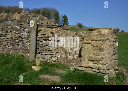 Footpath sign by a stone stile on the path between the Cotswolds villages of Swinbrook and Burford near Widford - Stock Image
