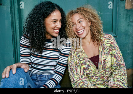 Portrait of two young smiling women with long curly black and blond hair, smiling and laughing. - Stock Image