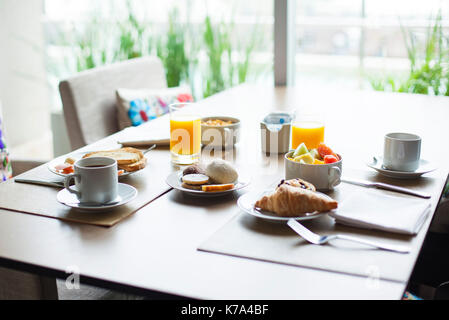 Breakfast of fruit and pastries on cafe table - Stock Image