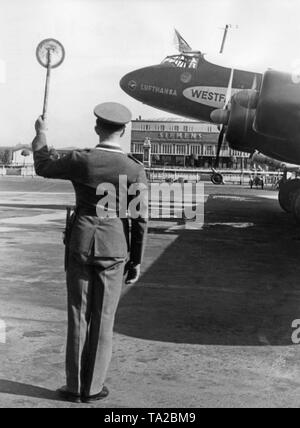 An official of the aviation authorities gives a Focke-Wulf FW 200 'Condor' of the Lufthansa (registration D-AETA, given name 'Westfalen') the flight permit. - Stock Image