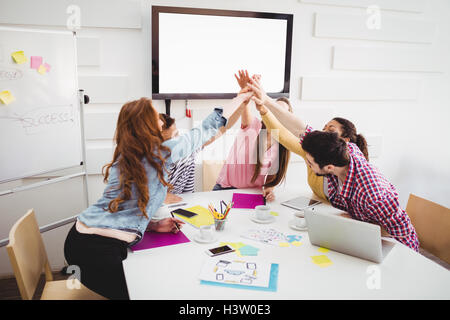 Business people giving high-five together in meeting at creative office - Stock Image