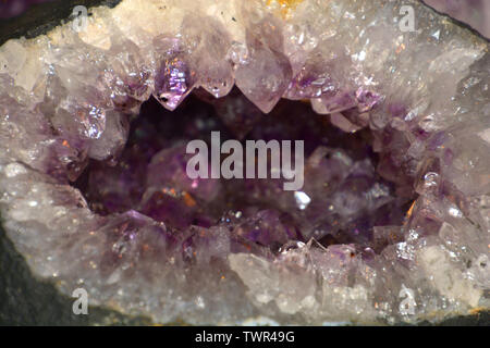 amethyst geode natural crystal gemstone macro shot purple background with bokeh effect, amethyst quartz in silver and purple - Stock Image