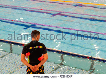 Poznan, Poland - January 26, 2019: Instructor standing with swim stick next to a pool during swimming lesson in the Termy Maltanskie. - Stock Image