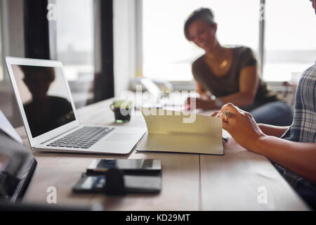 Women sitting at table in office - Stock Image