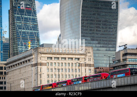 NOVEMBER 13, 2018, London, United Kingdom : Iconic new red London double decker passenger buses on London Bridge feat. Famous Office Buildings - Stock Image