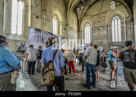 A tour guide leads a group of tourists through the old chapel in the Pope's Palace in the Provence region of Avignon, France. - Stock Image